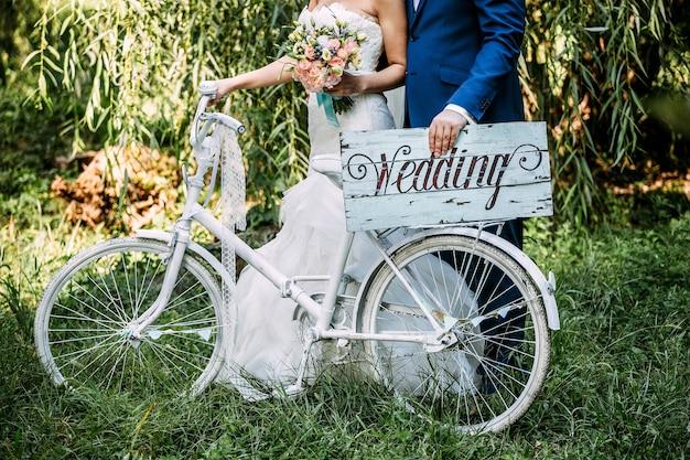 Bride and groom tenant une planche de bois avec mot de mariage dessus