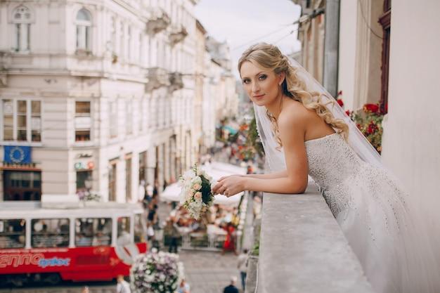 Bride sur le balcon avec la ville de fond