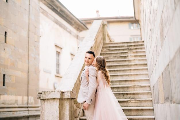 Bride hugs smiling groom de derrière les jeunes mariés se tiennent sur les marches d'un ancien bâtiment à bergame