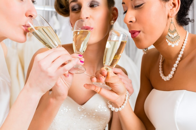 Brides buvant du champagne dans un magasin de mariage