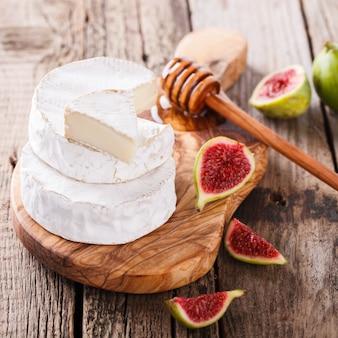 Brie sur une planche de bois avec figues fraîches et miel