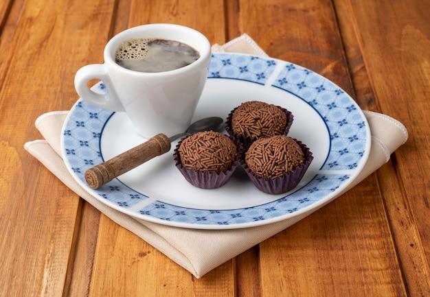 Brigadeiros brésiliens typiques sur une assiette avec une tasse de café sur une table en bois
