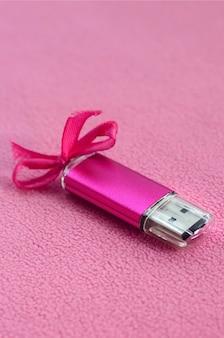 Brillant carte mémoire flash usb rose avec un arc rose se trouve sur