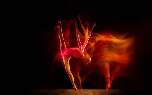 Brillant. jeune fille flexible isolée sur fond de studio noir en lumière mixte. artiste féminine de gymnastique rythmique pratiquant en action. exercices de souplesse, d'équilibre. grâce en mouvement, sport.