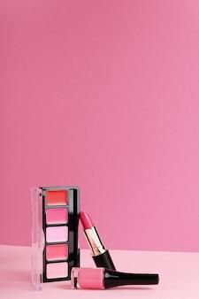 Brillant à lèvres, palette de fard à joues, rouge à lèvres sur fond rose vif.
