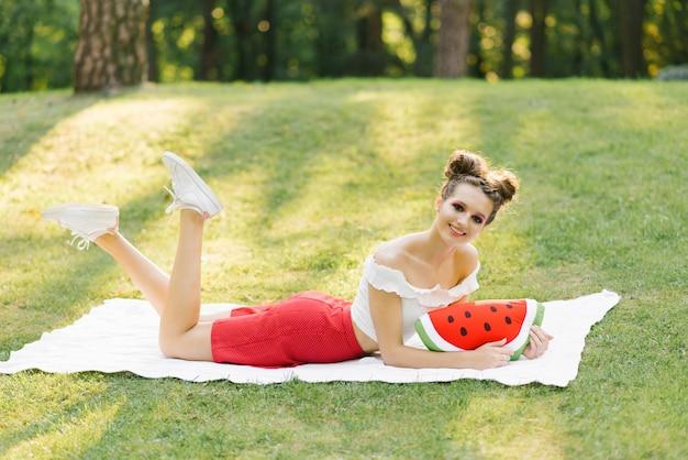 Brillante et jeune fille se trouve sur un plaid blanc sur une pelouse dans un parc