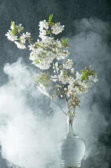 Brin de fleurs de cerisier en fumée et gouttes d'eau sur fond noir