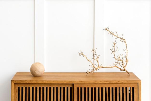 Brindille sèche sur une armoire en bois dans une pièce blanche