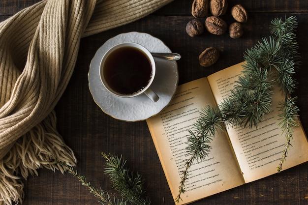 Brindilles et conifères près du thé et du livre