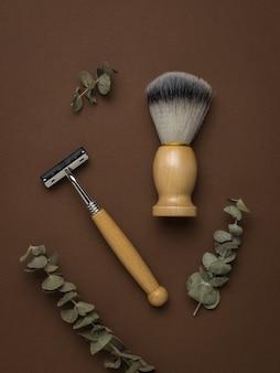 Brindilles d'eucalyptus et accessoires de rasage vintage sur fond marron. espace pour le texte. mise à plat.