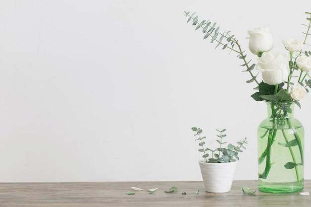 Brindilles d'eucalyptus et roses dans un vase en verre blanc