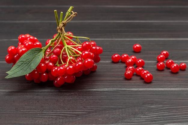 Brindilles de viorne attachées en bouquet. fruits rouges sur table. fond en bois sombre. vue de dessus