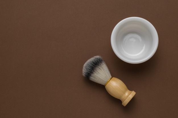 Brins d'eucalyptus, un rasoir en bois et une brosse avec un bol sur fond marron. mise à plat.