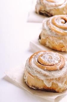 Brioches à la cannelle chaudes avec du glaçage à la crème au sucre sur un fond blanc sur du papier sulfurisé.