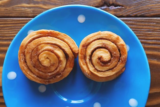 Brioches à la cannelle avec du sucre sur une assiette bleue.