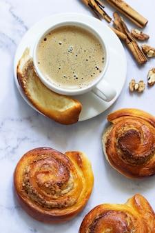 Brioches à la cannelle fourrées aux noix, servies avec du café. mise au point sélective.