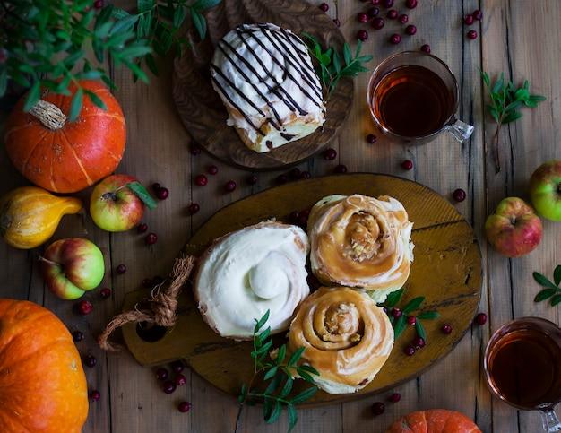 Brioches à la cannelle fraîches avec thé, citrouilles et pommes. vue d'en haut