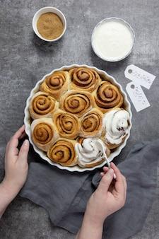 Brioches à la cannelle, petits pains dans un plat allant au four avec cassonade, sauce à la crème caillée et bâtons de cannelle. des mains féminines décorent les petits pains avec de la crème.