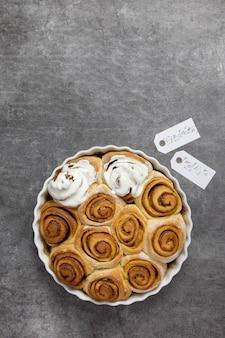 Brioches à la cannelle, petits pains dans un plat allant au four avec cassonade, sauce crème caillée sur béton foncé.