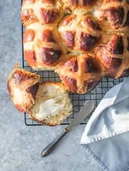 Brioches croisées chaudes avec du beurre. friandise traditionnelle de pâques