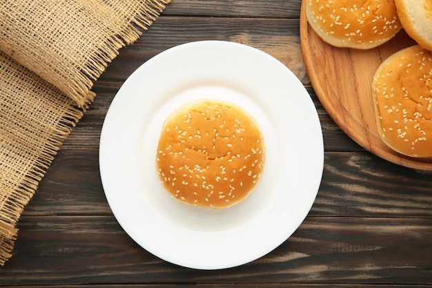 Brioches à hamburger en plaque sur fond marron. vue de dessus