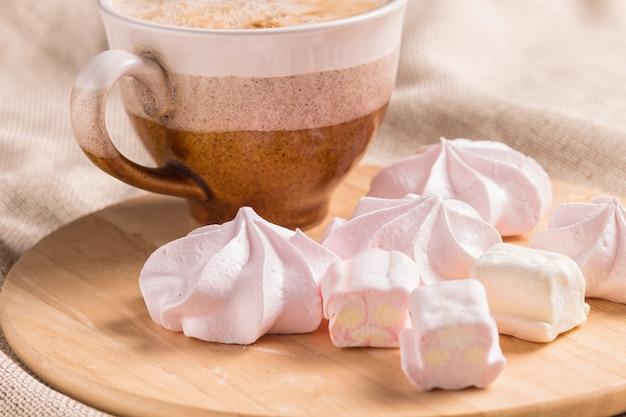 Brioches, meringues et tasse à café sur une planche de bois