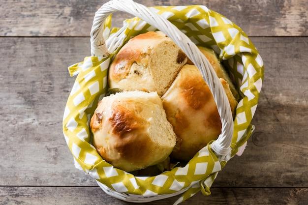 Brioches de pâques dans un panier sur une table en bois