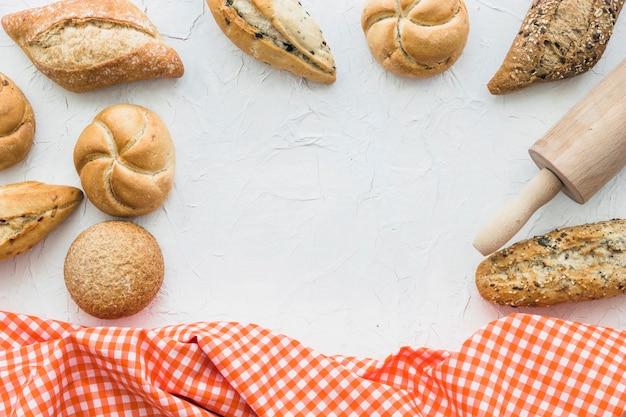 Brioches et rouleau à pâtisserie près de tissu