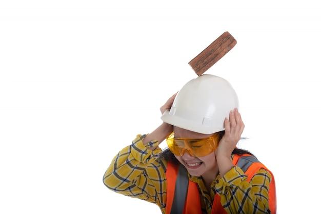 La brique de bloc de bâton est tombée sur la tête de la jeune femme ingénieur d'asie