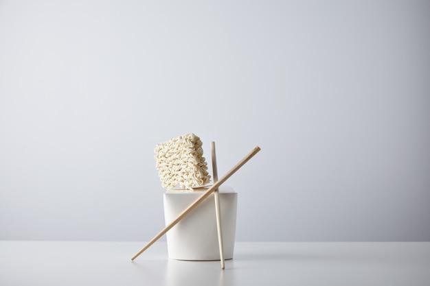 Brique de nouilles sèches compressées présenté sur le dessus de la boîte à emporter vierge avec des baguettes isolated on white au centre