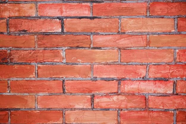 Brique rouge grunge dans le mur avec du mastic gris