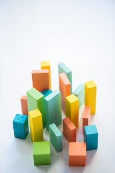 Briques et cubes en bois plat bleu, orange, jaune et vert qui composent le graphique en isolement avec copyspace ci-dessus