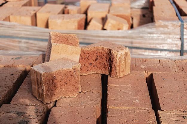 Briques en palettes sur un chantier de construction. matériaux de construction. brique rouge pour construire une maison.
