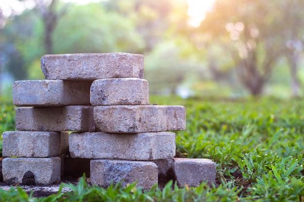 Briques de pavage et dalles sur l'herbe dans l'herbe