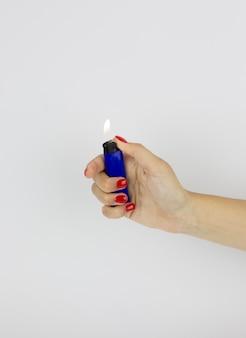 Briquet bleu avec le feu dans la main de la femme isolé sur fond blanc