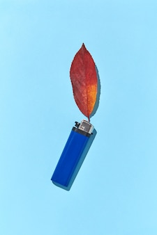 Briquet bleu avec feu de feuille rouge d'automne et ombres dures comme composition créative à la main
