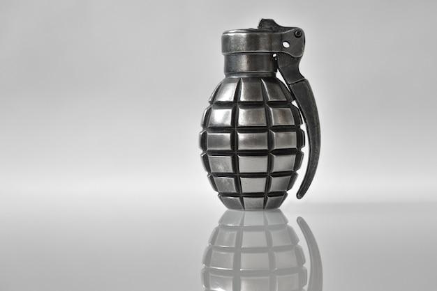 Un briquet comme une grenade à main sur fond gris avec un reflet.