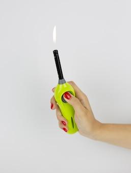Briquet polyvalent vert avec le feu dans la main de la femme isolé sur une surface blanche