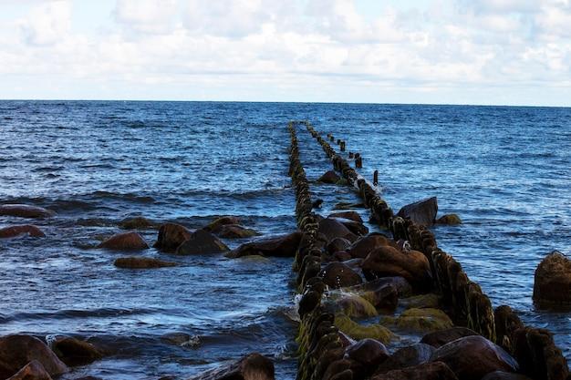 Brise-lames dans la mer baltique. barrière pour les vagues en bois. rivage
