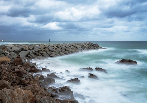 Brise-lames sur la plage journée nuageuse