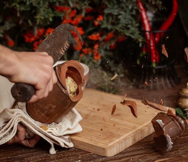 Briser un pot de poterie avec un grand couteau.