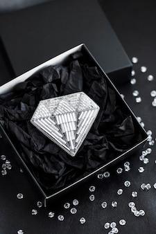 Broche brodée de perles de rocaille en forme de diamant sur une boîte cadeau noire sur une surface noire