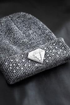 Broche brodée de perles de rocaille en forme de losange sur un bonnet tricoté sur une surface noire