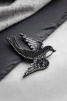 Broche brodée de perles de rocaille en forme d'oiseau hirondelle noir sur fond gary et noir