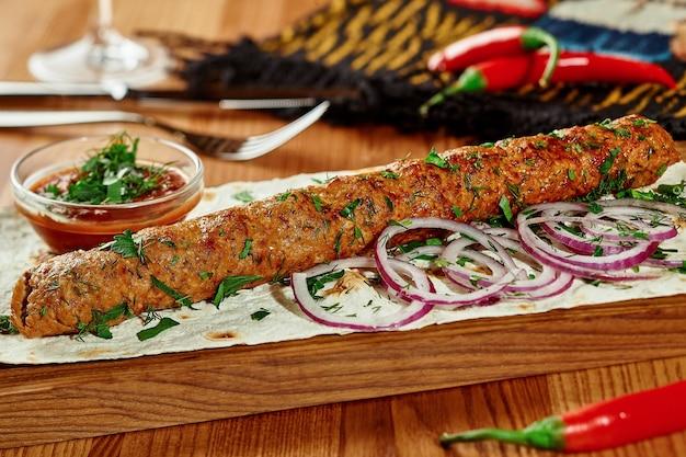 Brochette d'agneau avec oignon frais lavash mince et sauce satsebeli