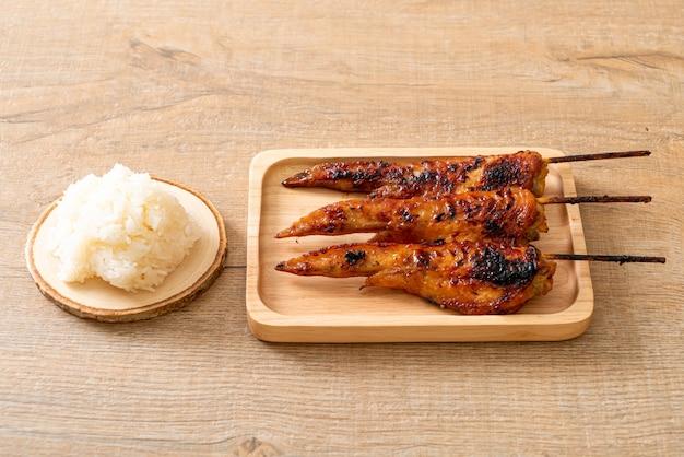 Brochette d'ailes de poulet grillé sur assiette avec riz gluant