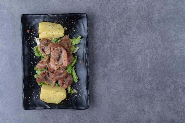 Brochette de boeuf et pommes de terre bouillies sur plaque noire.