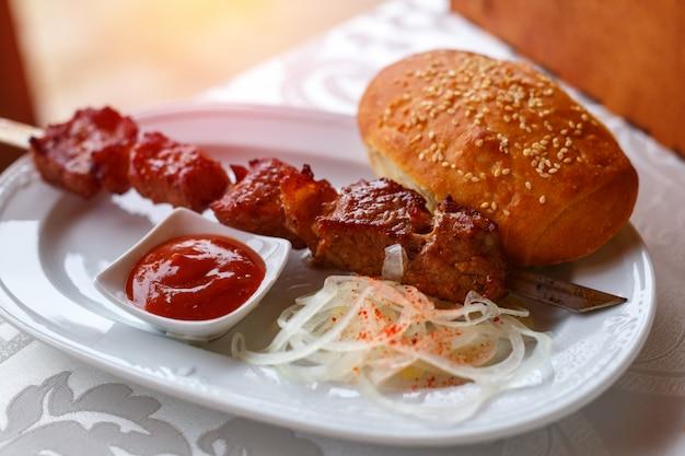 Brochette brochette allongée sur une assiette avec de la sauce