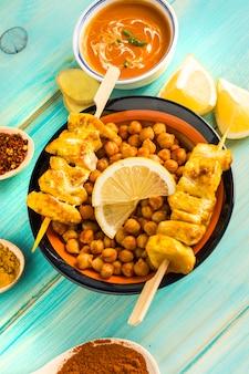 Brochette de pois chiches et poulet au milieu des condiments