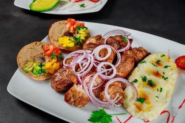 Brochette de porc servie avec purée de pommes de terre